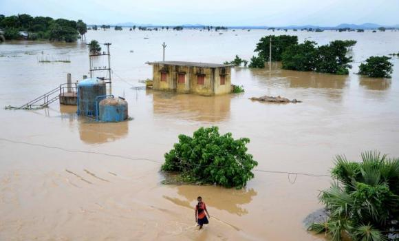 In this photograph taken on August 7, 2014, an Indian village youth makes his way through floodwaters at Kakharubasta village near Kanas block in Puri district, some 55 kilometers from Bhubaneswar.
