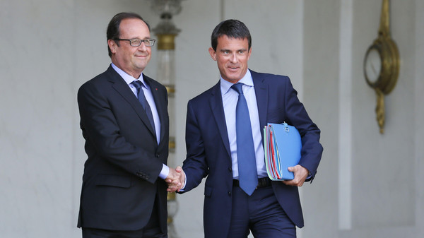French President Francois Hollande (L) and French Prime Minister Manuel Valls shaking hands at the Elysee presidential palace.