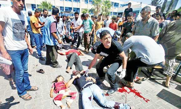 A man reacts as wounded and dead people lie on the ground following an Israeli airstrike at a UN-run school sheltering 3,000 displaced Gazans.