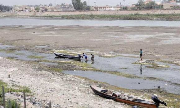 Iraqi men move a boat that was stuck on the banks of the Euphrates river in Twairij, roughly 20 kilometres east of Karbala, due to a decline in the water level after supplies were blocked by anti-government fighters who control access to a dam further upstream in conflict-hit Anbar province.
