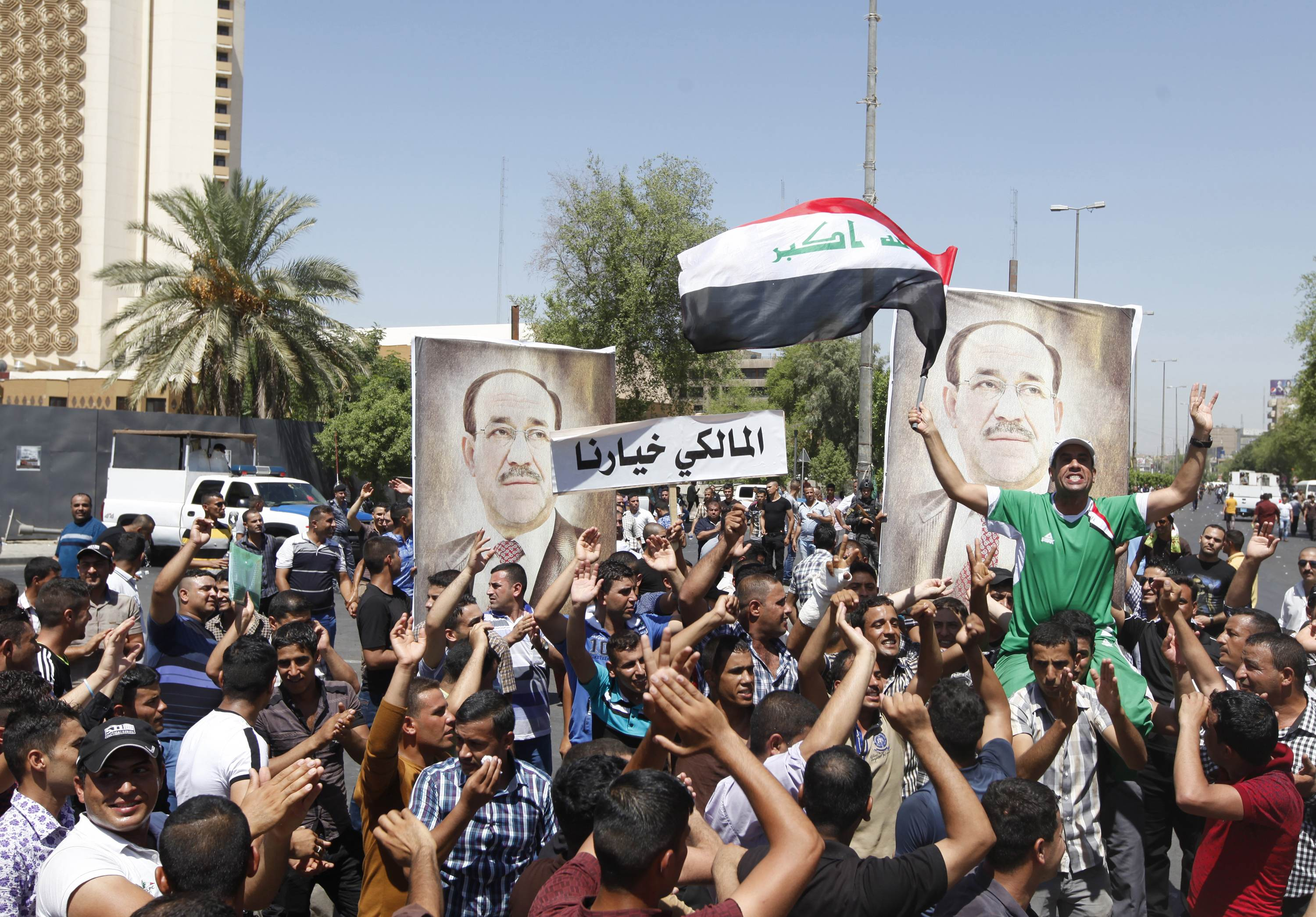 People with portraits of Iraqi Prime Minister Nouri al-Maliki gather at a rally in support of him in Baghdad August 11, 2014.