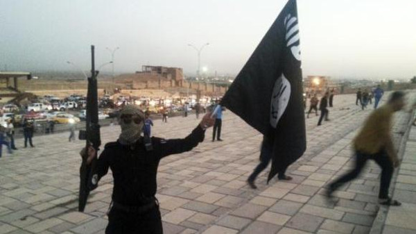 A fighter of the Islamic State of Iraq and the Levant (ISIL) holds an ISIL flag and a weapon on a street in the city of Mosul, June 23, 2014.