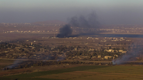 Smoke rises on both sides of the line dividing the Israeli-occupied Golan Heights from Syria during fighting near the Quneitra border crossing August 27, 2014.