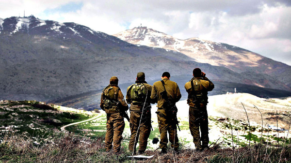 Israeli soldiers deployed on the border with Syria keep watch from the Israeli side of the border near the Druze village of Majdal Shams.