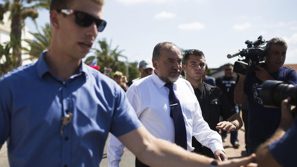 Israel's Foreign Minister Avigdor Lieberman (C) is surrounded by bodyguards during a visit with his Norwegian counterpart Borge Brende (not pictured) to the site where a rocket landed in Ashkelon July 16, 2014.