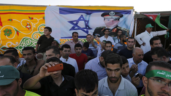 Supporters of the Jordanian Muslim Brotherhood stand in front of an Israeli flag bearing a portrait of Egyptian President Abdel Fattah al-Sisi during a rally in support of Palestinians in Gaza, in Amman August 8, 2014.