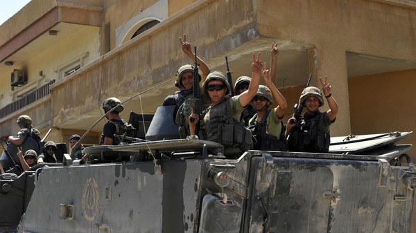Lebanese army soldiers flash victory signs while riding on armored carriers and military vehicles as they advance towards the Sunni Muslim border town of Arsal, in eastern Bekaa Valley as part of reinforcements.