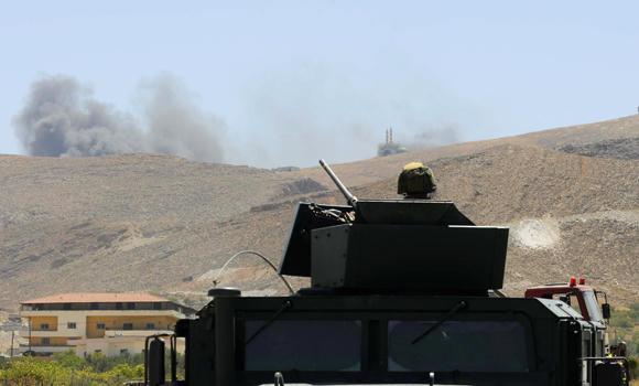 A Lebanese army soldier sits atop an army vehicle at the entrance of the border town of Arsal, in eastern Bekaa Valley, as smoke rises during clashes between Lebanese army soldiers and Syrian Islamist rebels on Monday.
