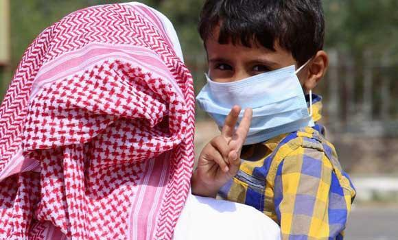 A boy wearing a mask is held by his father in Taif, in this June 7, 2014 photo.