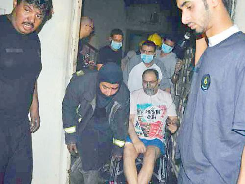 Rescue workers evacuate a disabled man and his family members from the burning house in Makkah's Um Al-Jood neighborhood.