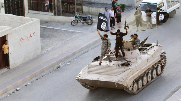 Militant Islamist fighters take part in a military parade along the streets of northern Raqqa province.