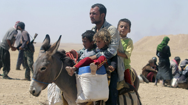 Displaced people from the minority Yazidi sect, fleeing violence from forces loyal to the Islamic State in Sinjar town, ride a donkey as they make their way towards the Syrian border, on the outskirts of Sinjar mountain, on August 10, 2014.