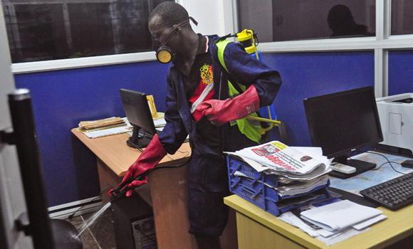 An employee of the Monrovia City Corporation sprays disinfectant inside a government building in a bid to prevent the spread of the deadly Ebola virus, in the city of Monrovia, Liberia, on Aug. 1, 2014. Because of the Ebola threat, Saudi Arabia has suspended the issuance of Umrah and Haj visas to pilgrims from Liberia, Sierra Leone and Guinea to prevent the spread of the disease.