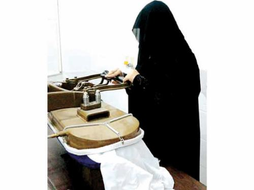 A Saudi woman presses clothes at Muhammad Al-Wabari's dry cleaning store in Al-Mansourah, east of Hofouf.