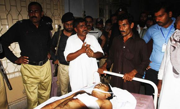 Relatives stand near the body of a supporter of Sufi cleric and leader of political party Pakistan Awami Tehreek (PAT) Muhammad Tahirul Qadri, who died at a hospital in Multan, from injuries after clashes with police in Bakhar in Punjab Province.