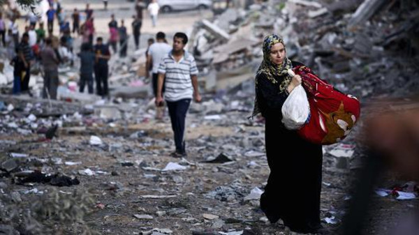 A Palestinian woman takes some of her belongings from her destroyed home in Gaza City was targeted by Israeli airstrikes.