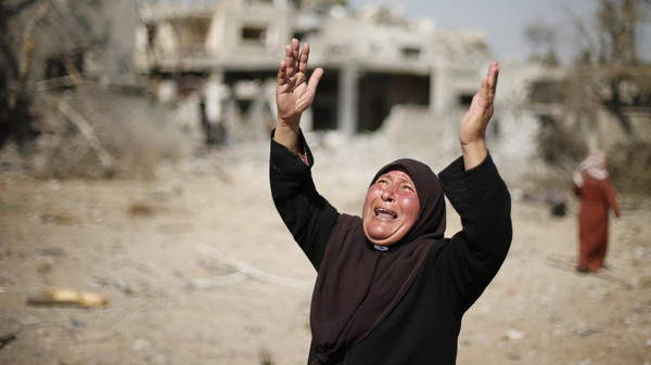 A Palestinian woman reacts upon seeing her destroyed house in Beit Hanoun town, which witnesses said was heavily hit by Israeli shelling and air strikes during Israeli offensive, in the northern Gaza Strip August 1, 2014.