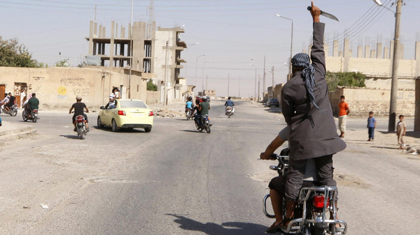 A man holds up a knife as he rides on the back of a motorcycle touring the streets of Tabqa city with others in celebration after Islamic State militants took over Tabqa air base, in nearby Raqqa city August 24, 2014.