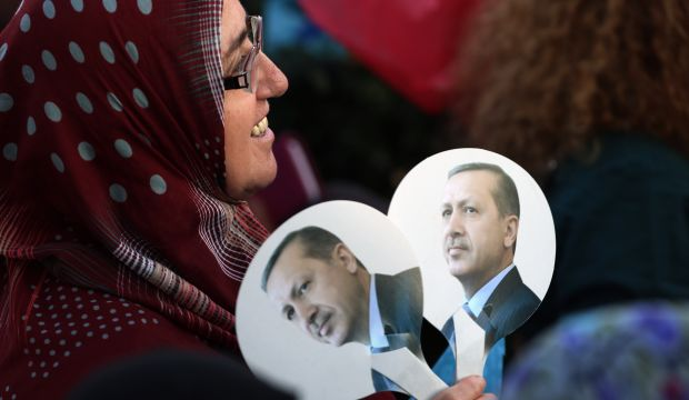 A supporter holds fans depicting Turkish Prime Minister Recep Tayyip Erdoğan, as she listens to him during a rally in Ankara, Turkey, on August 8, 2014.