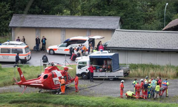 Rescue forces recover a victim of today's train crash, right, near Tiefencastel, Switzerland, on Wednesday.