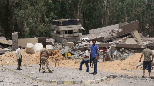 Members of the Weshavana Brigade survey the damage at a former Libyan Army camp known as Camp 27 following clashes between rival militias in the 27 district, west of Tripoli, August 10, 2014.