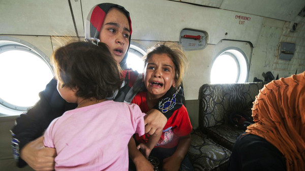 A woman and children react in a military helicopter after being evacuated by Iraqi forces from Amerli, north of Baghdad August 29, 2014.