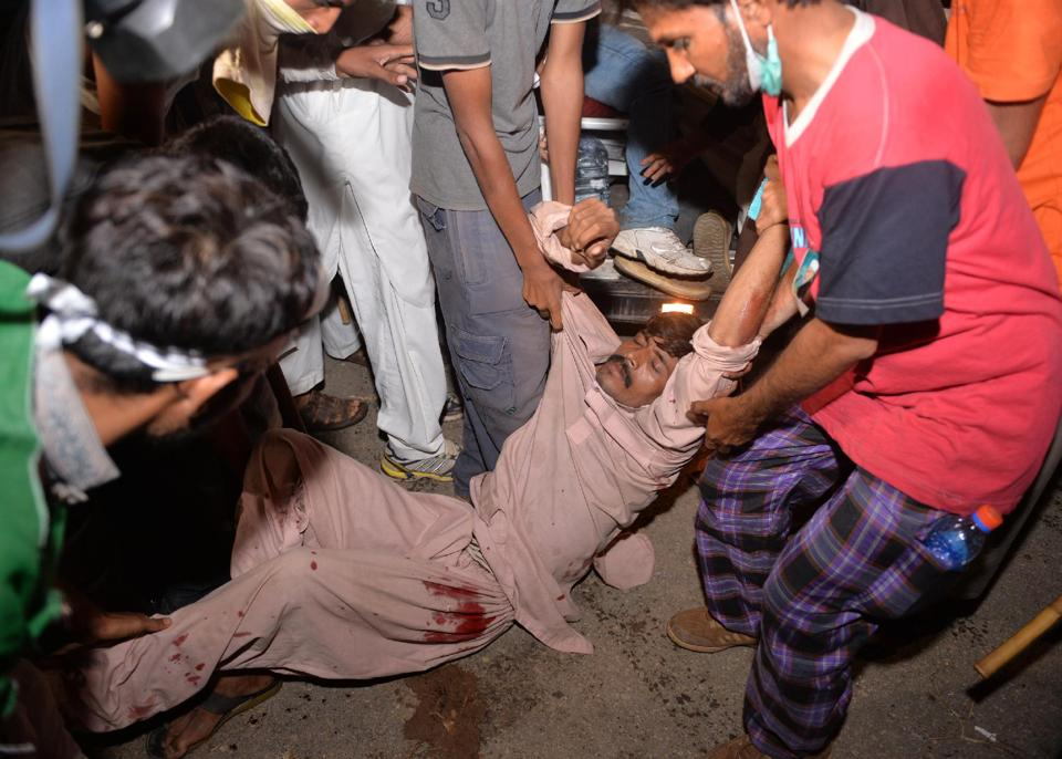 Opposition supporters carry a wounded protester in Islamabad.