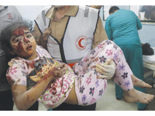A medic carries a wounded girl at hospital Khan Yunis in the southern Gaza Strip, following an Israeli military strike near her family home.