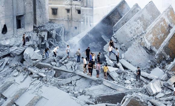 Palestinians inspect the remains of Al-Basha, a building that was destroyed by an Israeli air strike in Gaza City, in this August 26, 2014 photo.