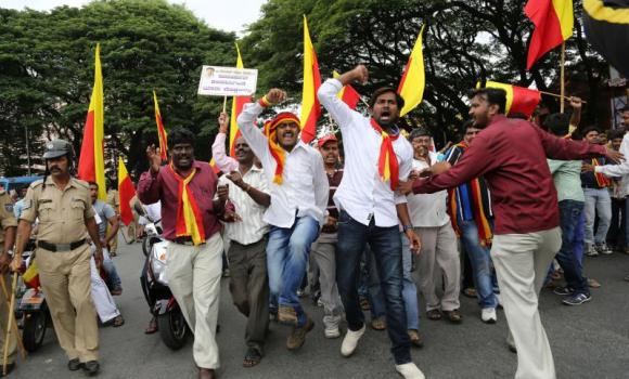 Activists of several political and social organizations of India's southern state of Karnataka wave state flags and shout slogans as they participate in a procession to protest against the rape of a six-year-old student in Bangalore, India, on July 31, 2014. Meanwhile, amid protests India's right-wing party Shiv Sena, threw its support behind a senior police official accused of rape by a model.