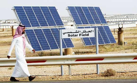 A Saudi man walks on a street past a field of solar panels at the King Abdulaziz city of Sciences and Technology, Al-Oyeynah Research Station, in this May 21, 2012 file photo.