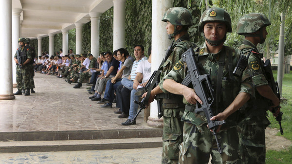 "Paramilitary policemen stand guard during a ceremony to award those who the authorities say participated in ""the crackdown of violence and terrorists activities"" in Hotan, Xinjiang Uighur Autonomous Region."