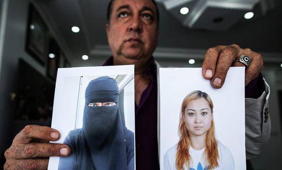 In this Sept. 19, 2014 photo, car salesman Sahin Aktan shows photos of his ex-wife Asiya Ummi Abdullah as he speaks during an interview at his lawyer's office in Istanbul, Turkey.