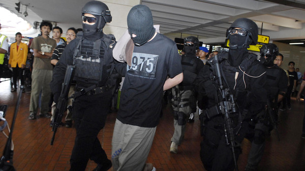 Elite Indonesian anti-terror police from Densus 88 escort four Turks arrested on arrival at Jakarta airport on September 14, 2014.