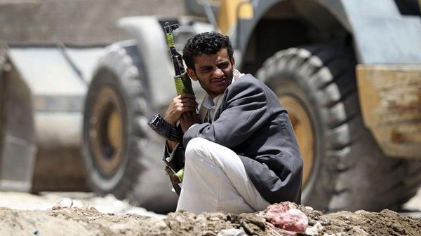 A tribal fighter carries a weapon as he squats near a bulldozer in Sanaa.