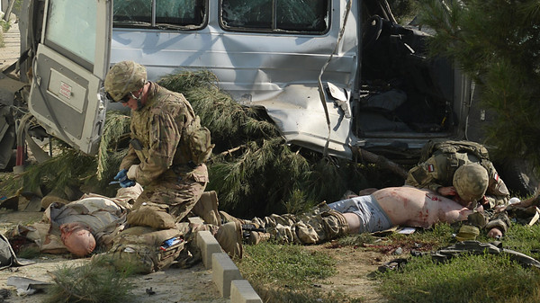 Foreign troops give first aid to foreign victims at the site of a suicide attack in Kabul on Sept. 16, 2014.