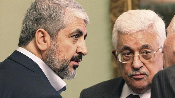 Hamas leader Khaled Meshaal (L) and Palestinian President Mahmoud Abbas talk with an official during a meeting in Cairo.