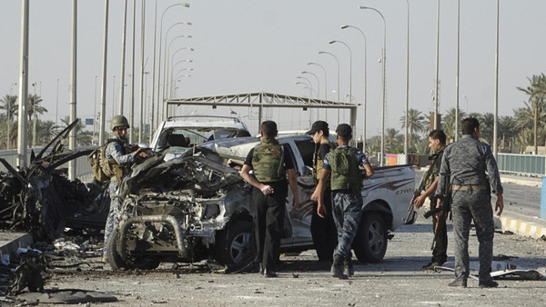 Iraqi security forces inspect the site of a suicide bombing on a bridge in Ramadi, west of Baghdad, September 17, 2014.