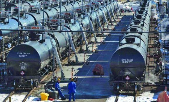 Irving Oil workers inspect rail cars carrying crude oil at the Irving Oil rail yard terminal in Saint John, New Brunswick.