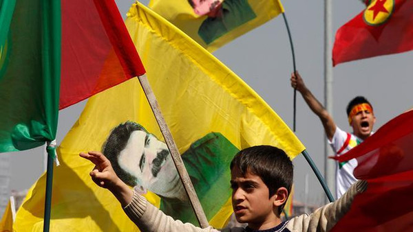 Kurds carry flags with PKK's jailed leader Abdullah Ocalan's picture printed on it