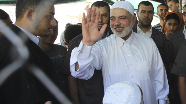 Senior Hamas leader Ismail Haniyeh waves after performing Friday prayers at a makeshift tent erected near the remains of a mosque, which witnesses said was hit by an Israeli air strike during a seven-week Israeli offensive, in Gaza City September 5, 2014.