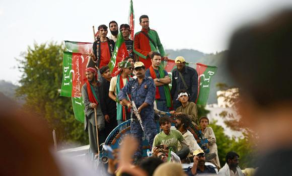 "Supporters of Imran Khan listen to his speech during an anti-government protest near the prime minister's residence in Islamabad on Tuesday. Pakistan's interior minister slammed violent anti-government protests as a ""revolt against the state"" as lawmakers backed beleaguered Prime Minister Nawaz Sharif."