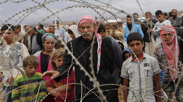 Syrian Kurds wait behind the border fences to cross into Turkey near the southeastern town of Suruc in Sanliurfa province September 28, 2014.