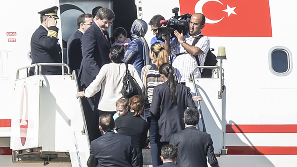 Turkish Prime Minister Ahmet Davutoglu (L) gets into his plane with freed hostages on September 20, 2014.