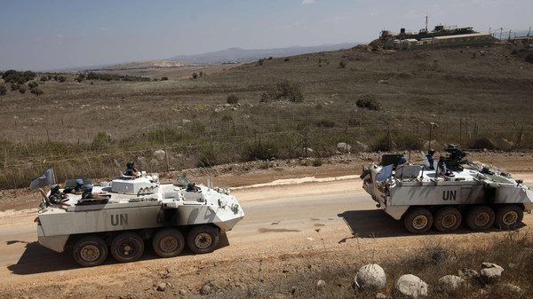 United Nations Disengagement Observer Force (UNDOF) armoured personnel carriers, including an armed one (R), escort a convoy of UNDOF vehicles leaving the Syrian side of the Golan Heights, on September 15, 2014.