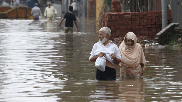 A couple wades through a flooded road after heavy rains in Lahore September 4, 2014. At least 73 people have been killed across Pakistan after heavy rains brought flash floods and caused homes to collapse in the Punjab and Kashmir regions.