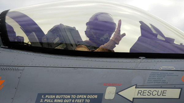 A Belgian F-16 fighter jet pilot gestures while taking off to join an international coalition fighting against ISIS.