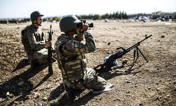 A Turkish soldier uses binoculars to check the Syrian border near the Mursitpinar border crossing on the Turkish-Syrian border in the southeastern town of Suruc, Sanliurfa province, on Saturday.