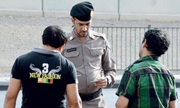 A police official checks the IDs of two expatriate workers.