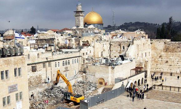 In this Feb. 6, 2013 file photo shows labourers use a bulldozer to raze a Israeli building in the Western Wall plaza of Jerusalem's Old City with the Dome of the Rock mosque and Al Aqsa mosque compound in the background.
